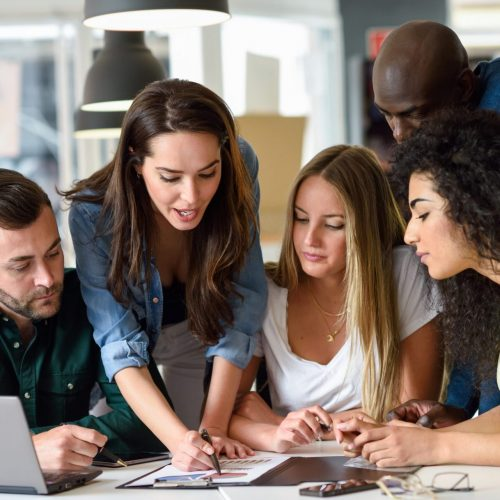Five young people studying on a white desk. Beautiful women and men working together wearing casual clothes. Multi-ethnic group.